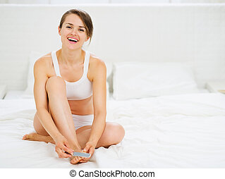Smiling woman sitting on bed and making manicure