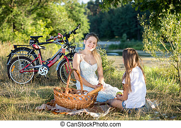 Smiling woman sitting on blanket under big tree with her daughter