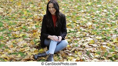 Smiling woman sitting on grass - Attractive smiling woman in...