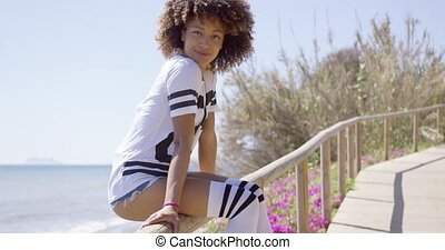 Smiling woman sitting on railings - Young woman in shirt and...