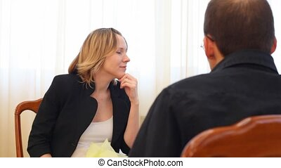 smiling woman sitting on seat against man
