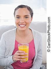 Smiling woman sitting on sofa and holding orange juice
