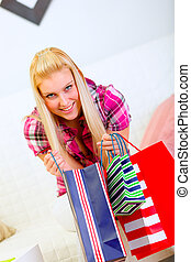 Smiling woman sitting on sofa and holding shopping bags in hands