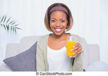 Smiling woman sitting on sofa holding glass of orange juice
