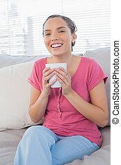 Smiling woman sitting on sofa holding mug of coffee