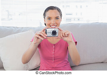 Smiling woman sitting on sofa taking a picture
