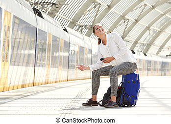 smiling woman sitting on suitcase using mobile