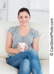 Smiling woman sitting on the couch and holding a mug