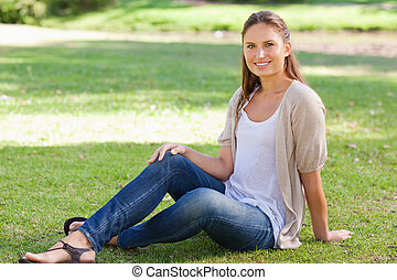 Smiling woman sitting on the lawn