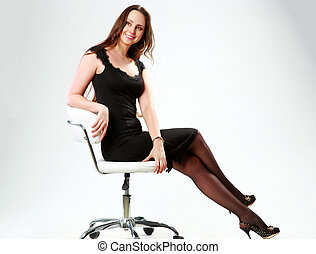 Smiling woman sitting on the office chair and looking away over gray background