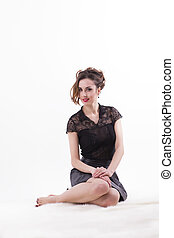 Smiling woman sitting on white background