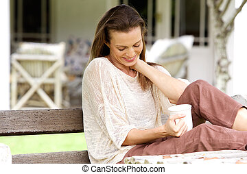 Smiling woman sitting outside with cup of coffee