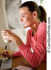 Smiling woman sitting with a cup of coffee