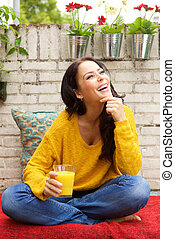 Smiling woman sitting with glass orange juice