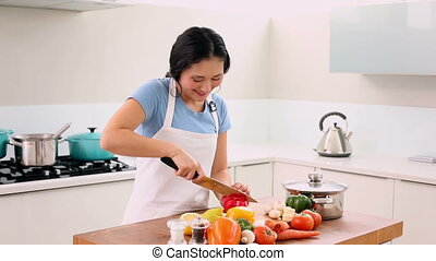 Smiling woman slicing vegetables wi