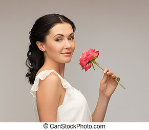 picture of smiling young woman smelling flower