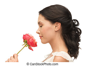 smiling woman smelling flower