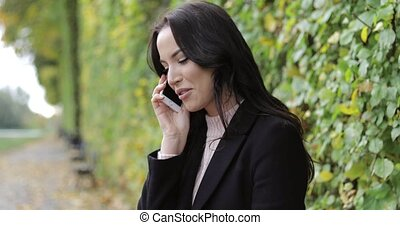 Smiling woman speaking on phone in park