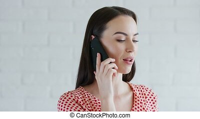 Smiling woman speaking on smartphone