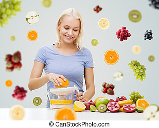 smiling woman squeezing fruit juice at home - healthy eating...