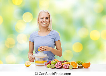 smiling woman squeezing fruit juice - healthy eating, ...