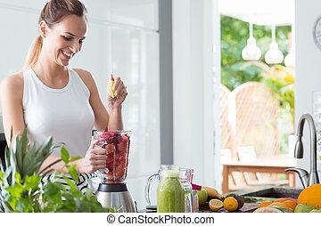 Smiling woman squeezing orange juice