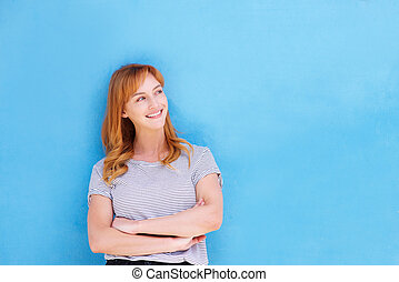 smiling woman standing against blue wall