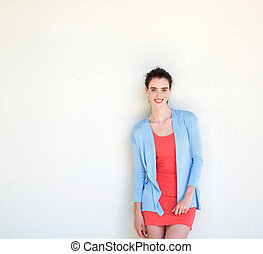 Smiling woman standing against white wall in dress