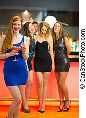 Smiling woman standing in front of her friends holding cocktail  looking at camera
