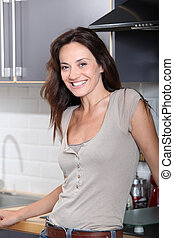 Smiling woman standing in kitchen