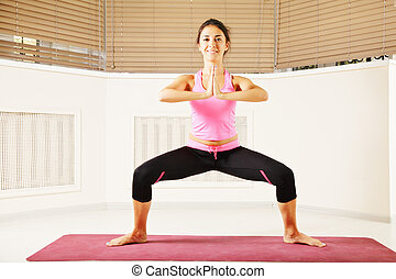 Smiling woman standing in yoga pose