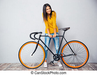 Smiling woman standing near bicycle - Full length portrait ...