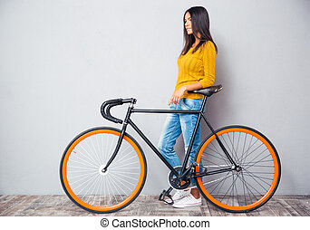Smiling woman standing near bicycle