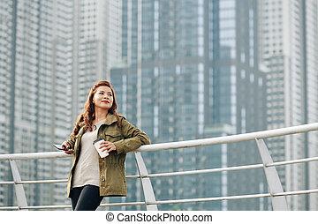 Smiling woman standing on bridge