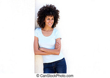 Smiling woman standing with arms crossed by white wall