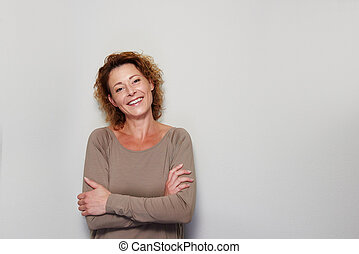 Smiling woman standing with arms crossed