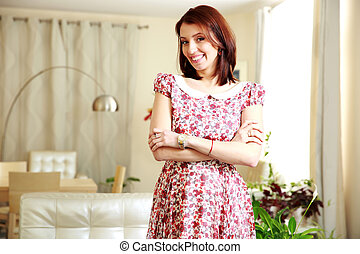 Smiling woman standing with arms folded at home