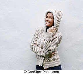Smiling woman standing with knitted wool sweater