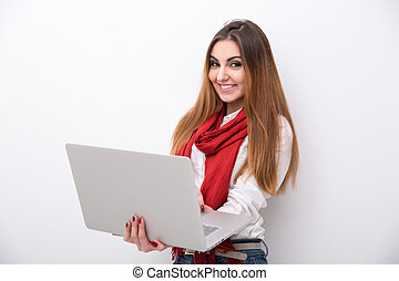 Smiling woman standing with laptop and looking at the camera