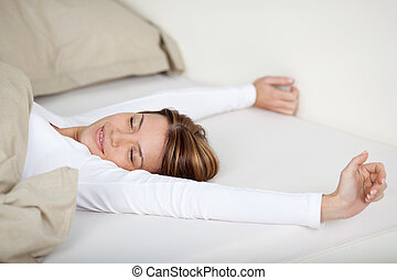 Smiling woman stretching in bed with a beautiful smile on ...