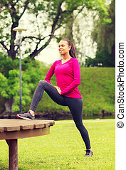 smiling woman stretching on bench outdoors