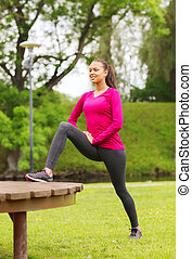 smiling woman stretching on bench outdoors - fitness, sport,...