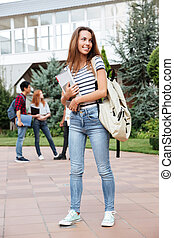 Smiling woman student with backpack walking outdoors