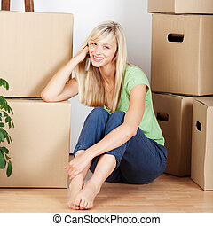 Smiling woman surounded by cardboard cartons