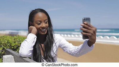 Smiling woman taking selfie on bench