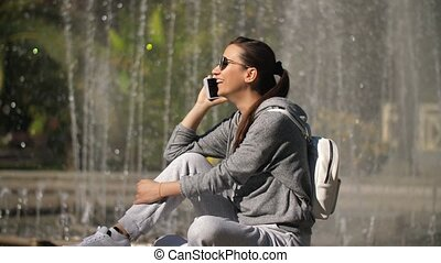Smiling woman talking by the phone on nature