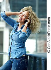 Smiling woman talking on phone with hand in hair