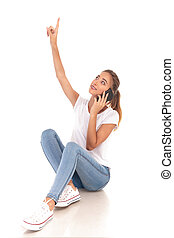 smiling woman talking on the phone is pointing up