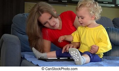 Smiling woman teaching little toddler girl using tablet pc sitting on bed.