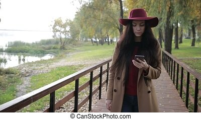 Smiling woman texting on phone in autumn park